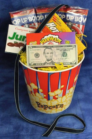 A movie theme gift basket that includes money for movie rentals.